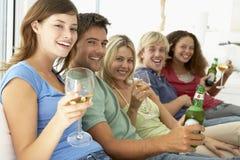 Amigos que miran la televisión junto Fotografía de archivo libre de regalías