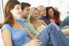 Amigos que miran la televisión junto Imágenes de archivo libres de regalías