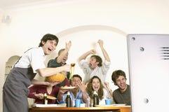 Amigos que miran la televisión y que celebran Foto de archivo libre de regalías