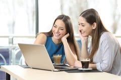 Amigos que miran medios en un ordenador portátil Foto de archivo libre de regalías