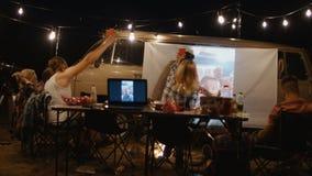 Amigos que miran película en la pantalla en sitio para acampar metrajes