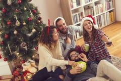 Amigos que miran películas de la Navidad imagen de archivo libre de regalías
