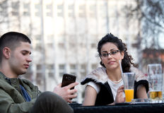 Amigos que miran smartphone en cafetería Fotos de archivo libres de regalías