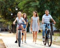 Amigos que montan las bicicletas y que caminan en el parque Fotos de archivo libres de regalías