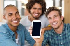 Amigos que muestran smartphone Foto de archivo