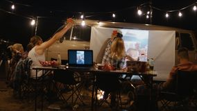 Amigos que olham o filme na tela no acampamento filme