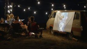 Amigos que olham o filme no acampamento video estoque