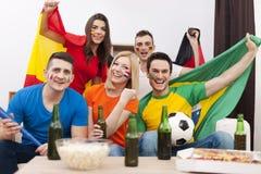 Amigos que olham o jogo de futebol na tevê Imagem de Stock