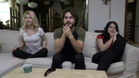 Amigos que olham sua mostra favorita em casa reagir com as emoções diferentes video estoque