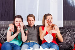 Amigos que olham um filme triste na tevê Foto de Stock Royalty Free