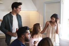 Amigos que pasan el tiempo junto que cuelga hacia fuera en la cocina Fotografía de archivo libre de regalías