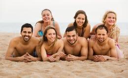 Amigos que ponen en la arena en la playa Imagenes de archivo