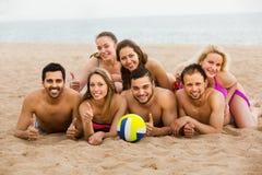 Amigos que ponen en la arena en la playa Imágenes de archivo libres de regalías