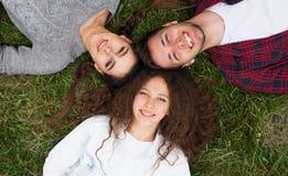 Amigos que ponen en la hierba que mira el cielo Fotografía de archivo libre de regalías