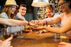 Amigos que ponen las manos encima de uno a en la barra Fotos de archivo libres de regalías