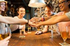 Amigos que ponen las manos encima de uno a en la barra Fotografía de archivo libre de regalías