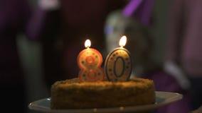 Amigos que presentan la torta de cumpleaños a la señora mayor sonriente, atmósfera de la celebración almacen de metraje de vídeo