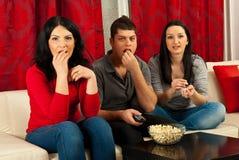 Amigos que prestam atenção à tevê e que comem popcorns Fotografia de Stock Royalty Free