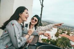 Amigos que ríen feliz en el balcón imagen de archivo