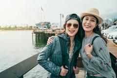Amigos que ríen feliz mientras que visita un muelle fotografía de archivo
