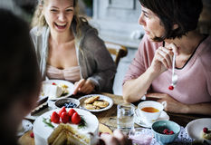 Amigos que recolectan junto en el disfrute h de las tortas de la consumición de la fiesta del té Imagen de archivo