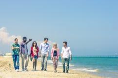 Amigos que recorren en la playa Imágenes de archivo libres de regalías