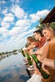 Amigos que refrigeram perto do lago Imagens de Stock Royalty Free