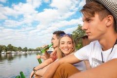 Amigos que refrigeram perto do lago Fotos de Stock Royalty Free