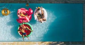 Amigos que relaxam em colchões infláveis na associação fotografia de stock