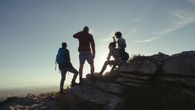 Amigos que relaxam na parte superior da montanha durante a caminhada video estoque