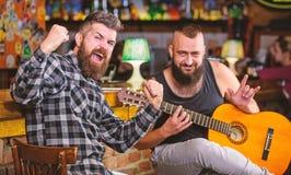 Amigos que relaxam no bar Concerto da m?sica ao vivo Guitarra do jogo do homem no bar Desempenho ac?stico no bar Farpado brutal d fotos de stock royalty free