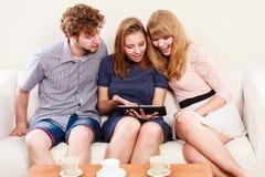 Amigos que relaxam o Internet da consultação na tabuleta Foto de Stock