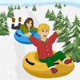 Amigos que resbalan abajo en los tubos de la nieve Fotografía de archivo