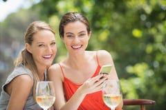 Amigos que riem ao usar o telefone celular no restaurante imagem de stock royalty free