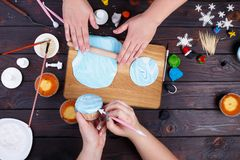 Amigos que rolam a mástique dos confeitos e que decoram os queques, vi fotografia de stock royalty free