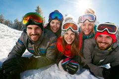 Amigos que se divierten el día de fiesta del esquí en montañas Foto de archivo
