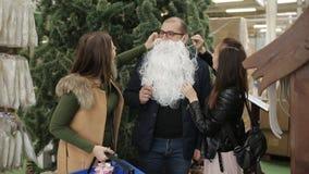 Amigos que se divierten en decoraciones de la Navidad de la venta Los amigos intentan encendido la barba de Papá Noel almacen de metraje de vídeo