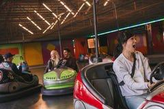 Amigos que se divierten en los coches de parachoques en parque de atracciones Foto de archivo