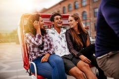 Amigos que se divierten en paseo del triciclo Imagen de archivo libre de regalías