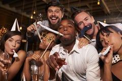 Amigos que se divierten que celebra el Año Nuevo en una barra, cierre para arriba Foto de archivo