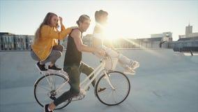 Amigos que se divierten un paseo en una bicicleta metrajes