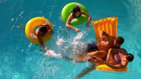 Amigos que se divierten y que salpican en piscina junto almacen de metraje de vídeo