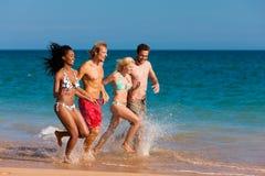 Amigos que se ejecutan el vacaciones de la playa Imagen de archivo libre de regalías