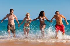 Amigos que se ejecutan el vacaciones de la playa Foto de archivo libre de regalías
