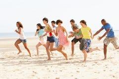 Amigos que se ejecutan a lo largo de la playa junto Imagen de archivo
