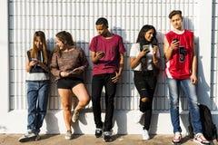 Amigos que se enfrían hacia fuera junto usando smartphone Imagen de archivo
