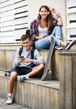 Amigos que se relajan con los teléfonos móviles Fotografía de archivo libre de regalías
