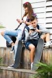Amigos que se relajan con los teléfonos móviles Fotos de archivo