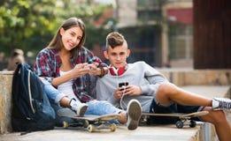 Amigos que se relajan con los teléfonos móviles Foto de archivo libre de regalías