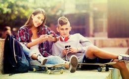 Amigos que se relajan con los teléfonos móviles Imagen de archivo